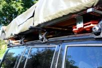 2 sandstegar, campingbord och köksbänk under tältet